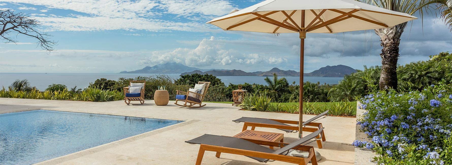 A lounge chair beside a pool with Nevis ocean and mountains in the background