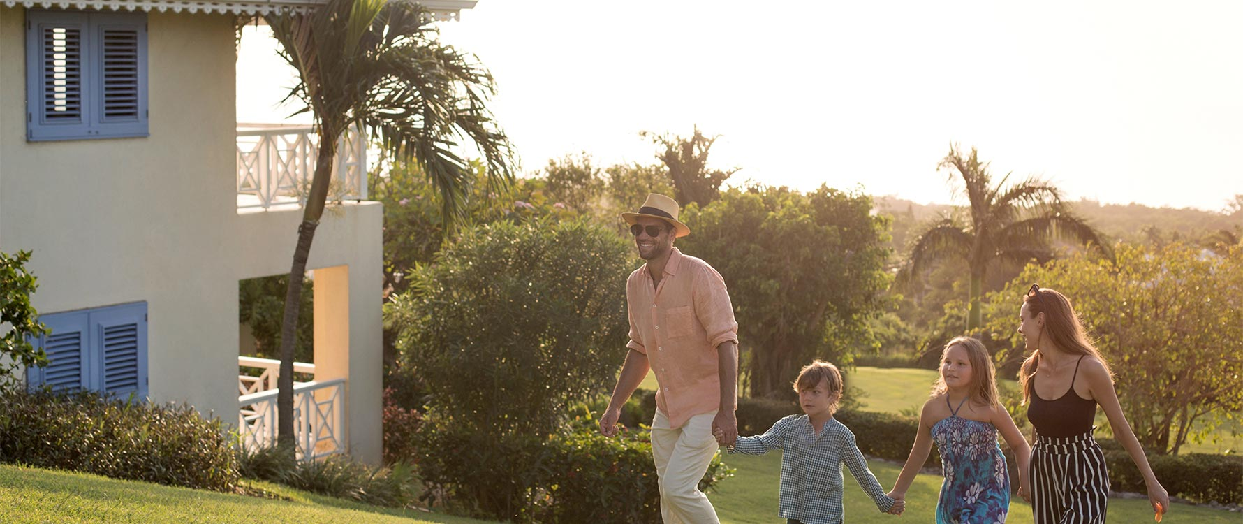 A family of four walks up a slope with a villa and lush greenery in the background.