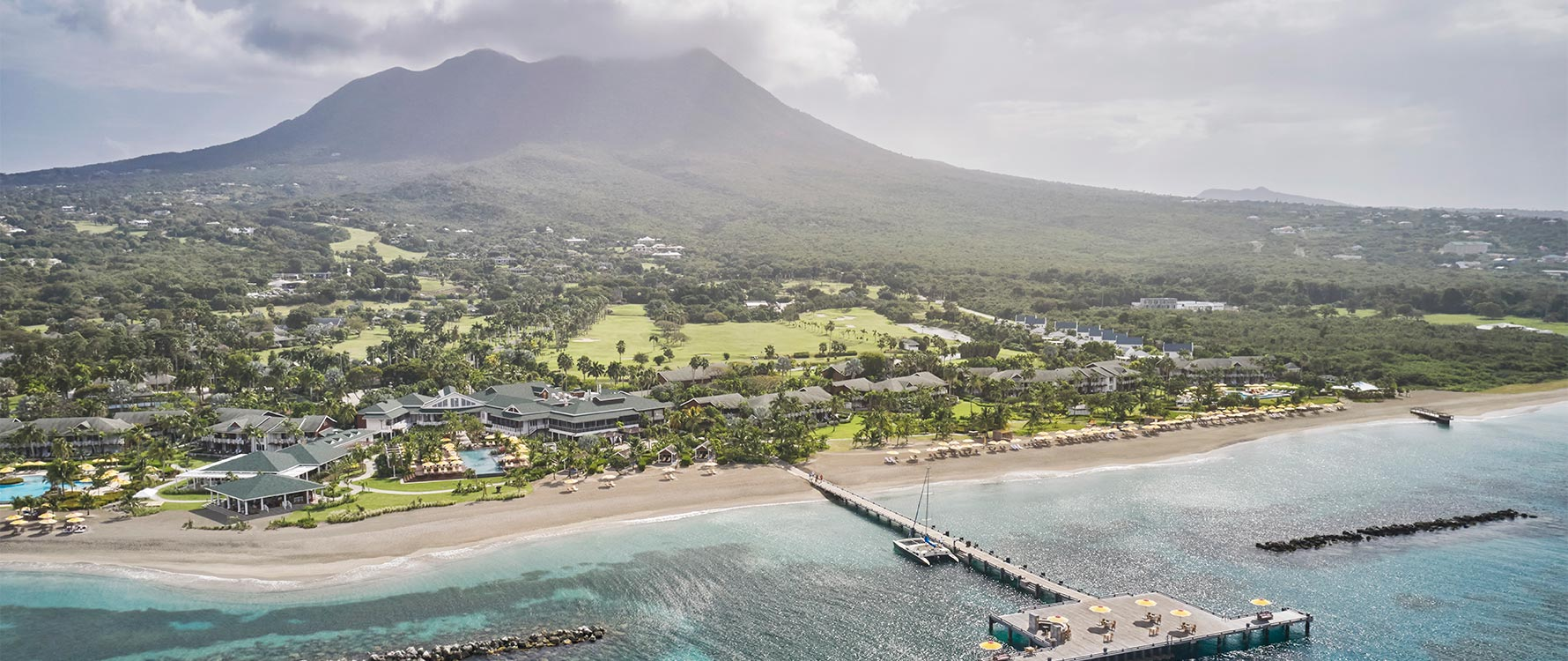 The island of Nevis with the resort in the foreground and the towering volcanic mountain in the background
